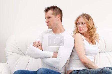 Young sad couple sitting on sofa Back to back over...
