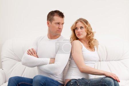 Young sad couple sitting