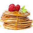 Small pancakes topped with honey, raspberries and ...