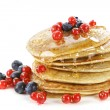 Small pancakes topped with honey, red currants and...