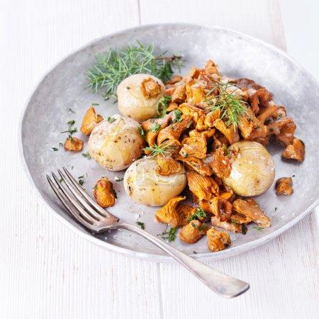Photo pour Chanterelles frits avec pommes de terre et oignon sur le fond en bois blanc - image libre de droit