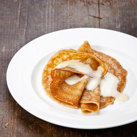 Sweet pancakes on plate with condensed milk on tab...