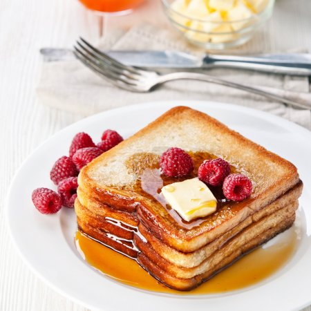 French toast with raspberries, maple syrup and butter