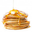 Stack of Small pancakes in syrup on white backgrou...