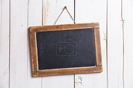 Photo for Vintage slate chalk board hanging on wooden background - Royalty Free Image