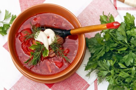 Hearty bowl of homemade red borsch with sour cream and parsley