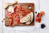 """Постер, картина, фотообои """"разделочная доска из вяленого мяса, сыра и оливкового"""""""
