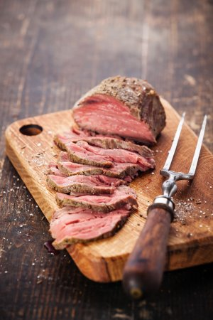Photo for Roast beef on cutting board and meat fork - Royalty Free Image