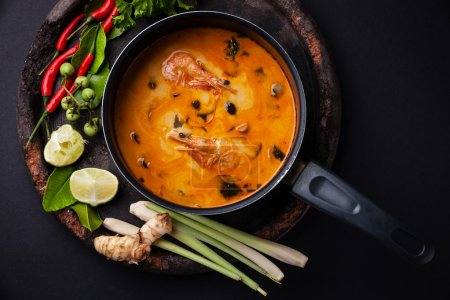 Spicy Thai soup Tom Yam with Ingredients on dark b...