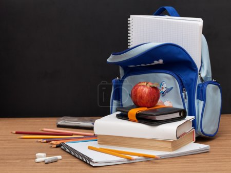 Photo for School Supplies with apple on black desk background - Royalty Free Image