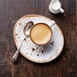 Espresso cup with milk on wooden background...