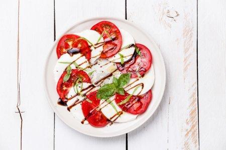 Photo pour Salade Caprese tranches de tomate et mozzarella avec des feuilles de basilic sur fond de bois blanc - image libre de droit