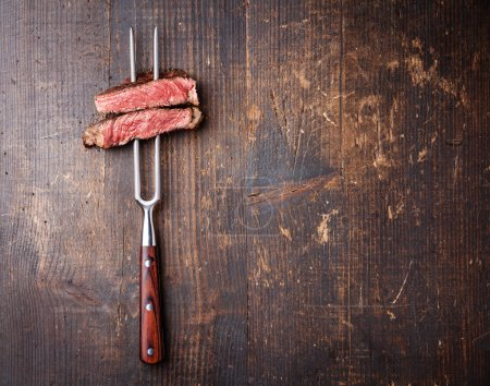 Photo for Slices of beef steak on meat fork on dark wooden background - Royalty Free Image