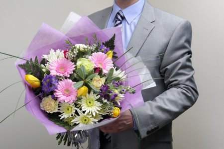 Photo for Businessman wearing a suit holding a bouquet of flowers - Royalty Free Image