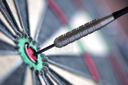 Photo for Dart in bulls eye of dartboard with shallow depth of field concept for hitting target - Royalty Free Image