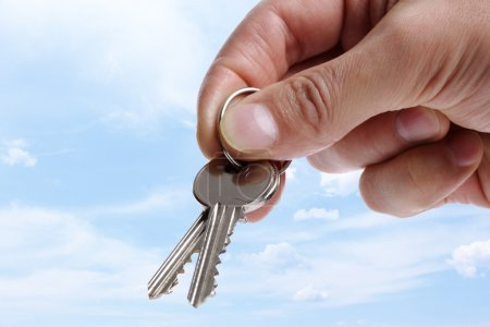 Photo for Handing over new house keys on blue sky background - Royalty Free Image