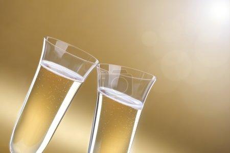 Foto de Tostar una celebración con copas de champaña sobre fondo de oro para copia - Imagen libre de derechos