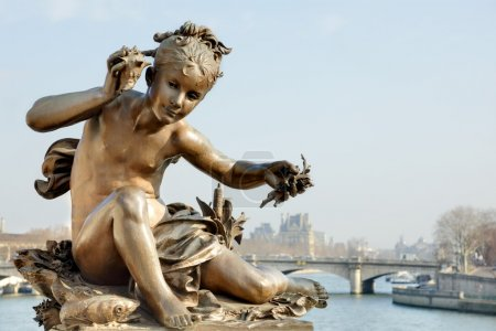 Photo for Bronze statue of a cherub on Pont Alexandre III bridge in Paris with the River Seine and The Louvre in the background - Royalty Free Image