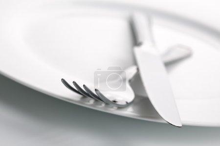 Photo pour Assiette en porcelaine blanche avec couteau en argent croisé et couverts de fourchette, profondeur de champ peu profonde avec accent sur la pointe de la fourchette - image libre de droit