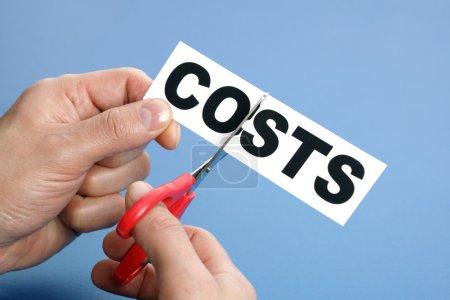 Photo pour Ciseaux coupant le mot coût concept de récession ou de crise de crédit - image libre de droit