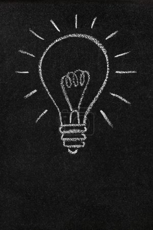 Photo for A lightbulb drawn on a chalkboard symbolizing ideas, inspiration and creativity with blank space for copy - Royalty Free Image