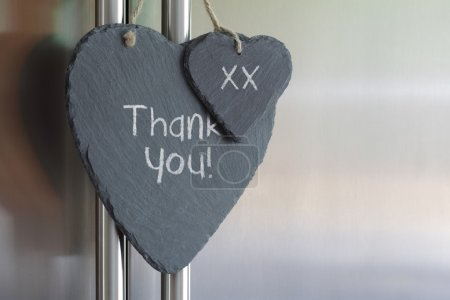 Photo for Thank you note written in chalk on a slate heart hanging on a refrigerator door - Royalty Free Image