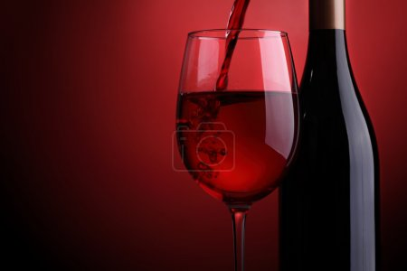 Photo for Red wine being poured into a glass with bottle against a red background - Royalty Free Image