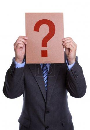 Photo pour Homme d'affaires détenant un point d'interrogation signe devant son visage sur fond blanc - image libre de droit