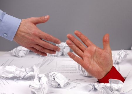 Photo for Businessman drowning in paperwork reaching for assistance and support - Royalty Free Image