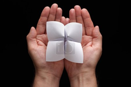 Photo for Origami fortune teller with blank choices in cupped hands - Royalty Free Image