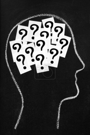 Photo pour Processus de pensée, de decicions ou de confusion. points d'interrogation à l'intérieur de la tête de la craie sur le tableau noir - image libre de droit