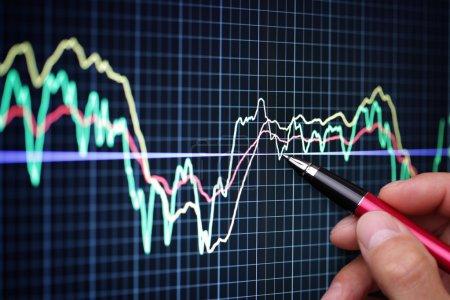 Photo pour Pointant sur le graphique d'analyse financière sur écran d'ordinateur avec stylo - image libre de droit