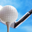 Golf club and golf ball about to tee off against a...