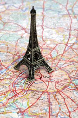 Photo for Statue of travel destination Eiffel Tower on a road map of Paris - Royalty Free Image