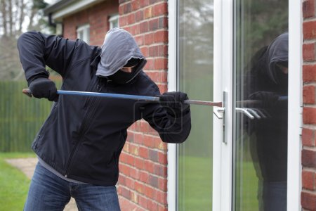 Photo for Burglar breaking into a house window with a crowbar - Royalty Free Image