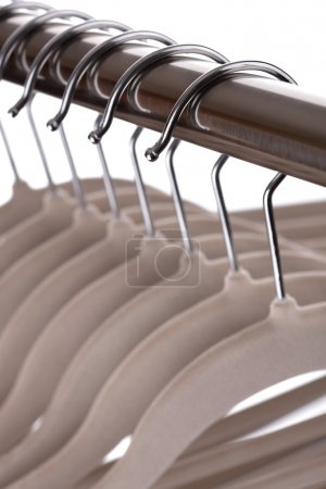 Photo for Empty coat hangers on metal clothes rail against white background - Royalty Free Image