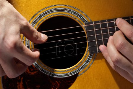 Photo for Acoustic guitarist playing guitar close up on fretboard and soundhole - Royalty Free Image