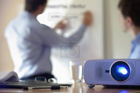 Photo pour Conférence d'affaires ou conférence avec un homme d'affaires écrivant sur tableau blanc et projecteur lcd au premier plan - image libre de droit