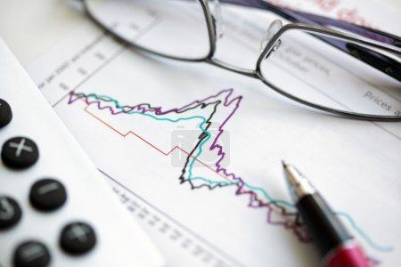 Photo pour Lunettes, stylo et calculatrice sur actions et actions graphique financier - image libre de droit