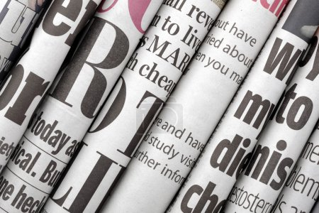 Photo for Newspaper headlines shown side on in a stack of daily newspapers - Royalty Free Image