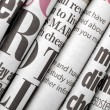 Newspaper headlines shown side on in a stack of da...