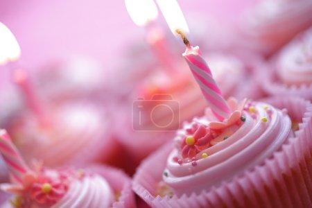 Photo pour Cupcakes roses d'anniversaire avec des bougies allumées - image libre de droit