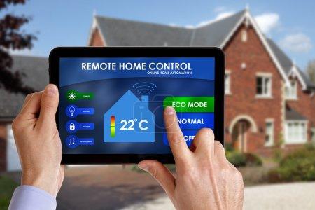Photo pour Détient un contrôleur d'énergie intelligente ou un système de domotique en ligne de télécommande d'origine sur une tablette numérique. tous les graphiques d'écran composés - image libre de droit