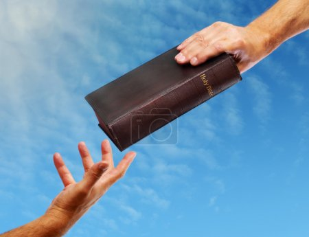 Photo for Passing over the bible hand giving a bible to another reaching out - Royalty Free Image