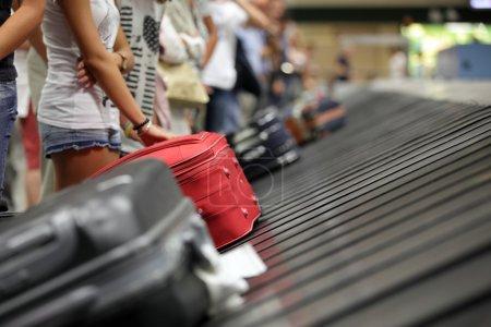 Photo pour Valise sur la courroie transporteuse de bagages dans la réclamation de bagages à l'aéroport - image libre de droit