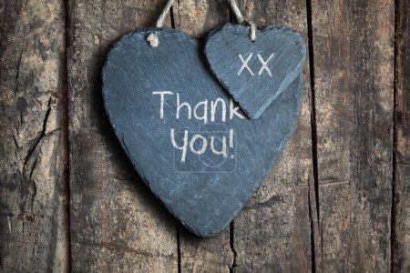 Photo pour Note de remerciement écrite à la craie sur un cœur d'ardoise accroché sur un fond de bois - image libre de droit