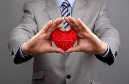 Photo pour Man holding a red woolen heart concept for valentine's day, business customer care, charity, social and corporate responsibility - image libre de droit