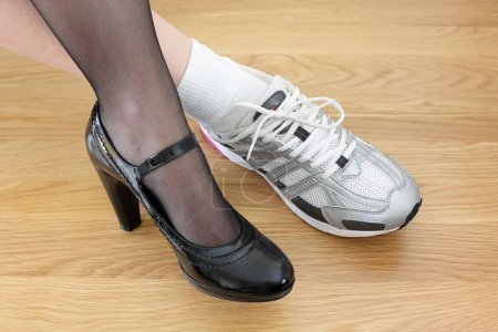 Woman wearing one business shoe and sports shoe co...