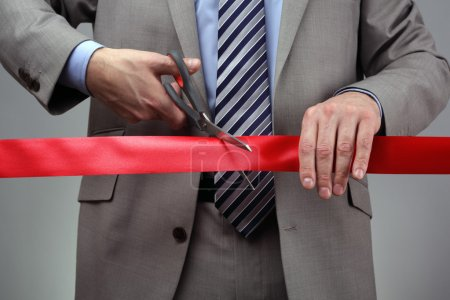 Photo for Cutting a red ribbon with scissors concept for new business venture or opening ceremony - Royalty Free Image