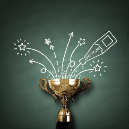 Photo pour Trophée ou coupe de championnat de première place devant le tableau noir avec champagne et feux d'artifice concept pour gagner et réussir - image libre de droit
